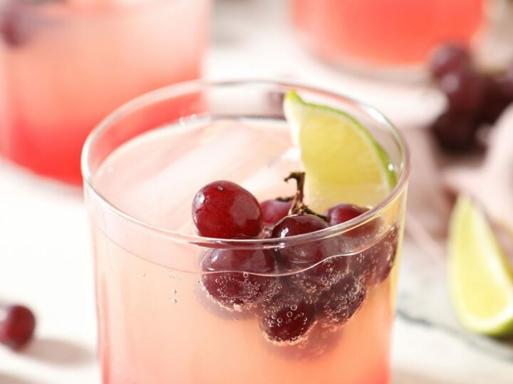 A cocktail with fresh grapes and a lime floating in it on marble