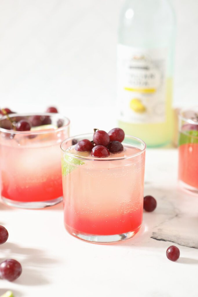 Two grape shrub cocktails on marble with grape garnishes