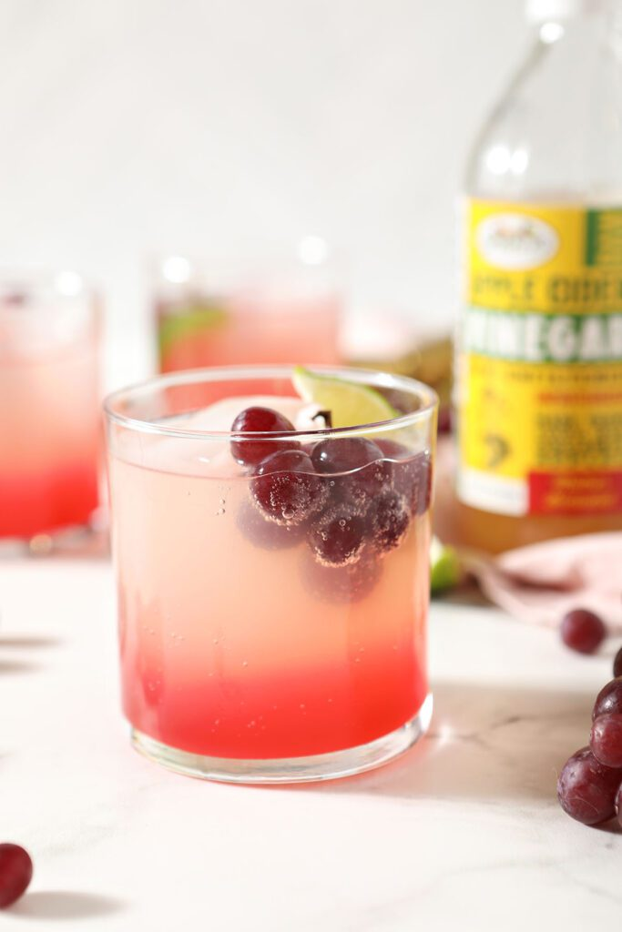 A pink mocktail garnished with fresh grapes and a lime wedge