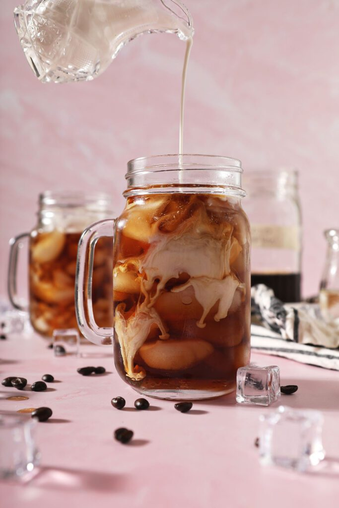 Homemade vanilla sweet cream pours into a glass of cold brew