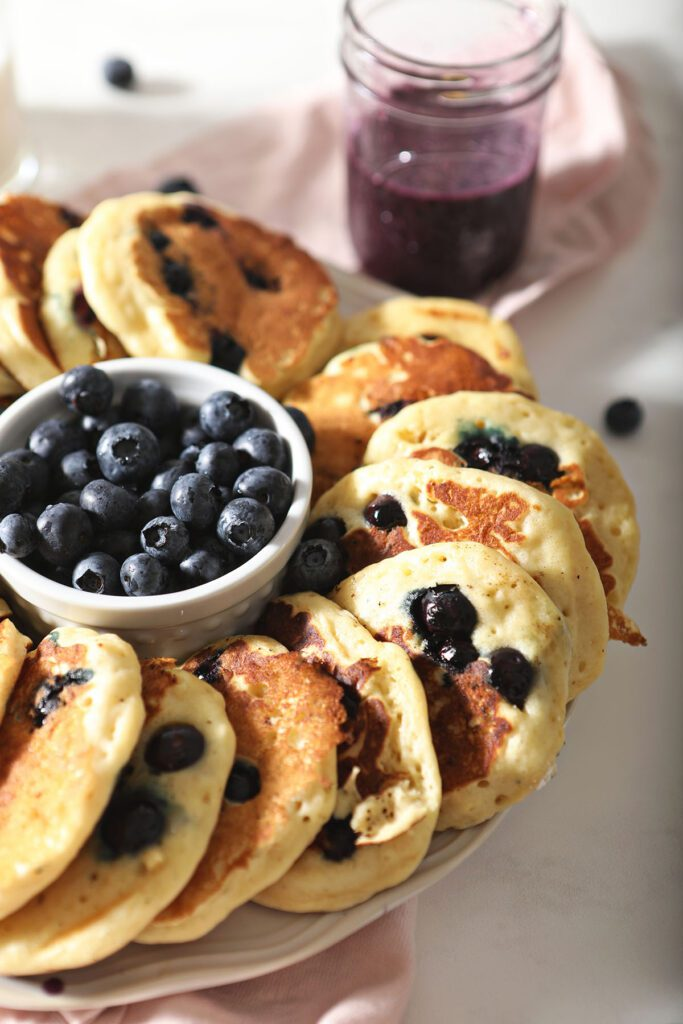 A plate of blueberry pancakes with fresh blueberries