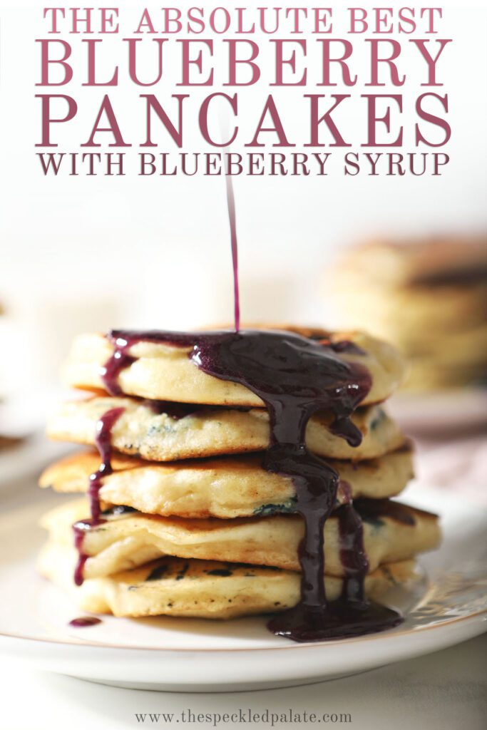 Syrup pours onto a stack of pancakes with the text the absolute best blueberry pancakes with blueberry syrup