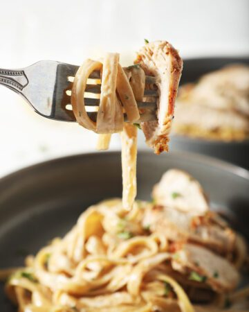 A fork holds a bite of chicken alfredo pasta