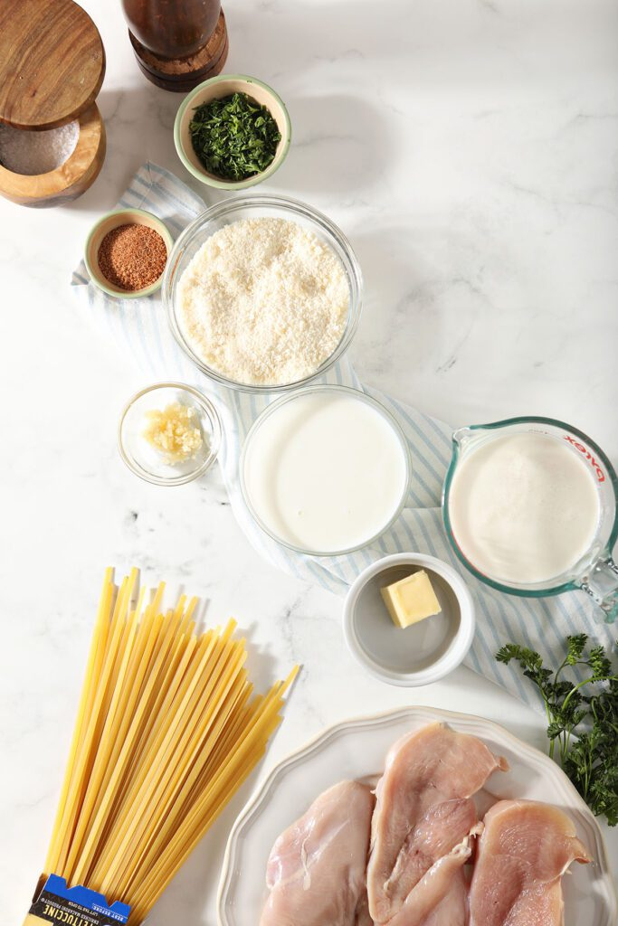 Ingredients to make a pasta dish in bowls on marble