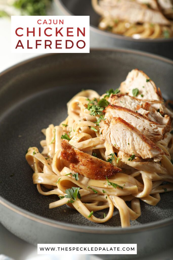 Close up of a bowl of pasta with chicken breast with the text cajun chicken alfredo