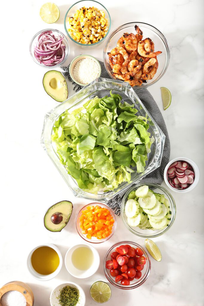 Ingredients to make a salad recipe in bowls on marble