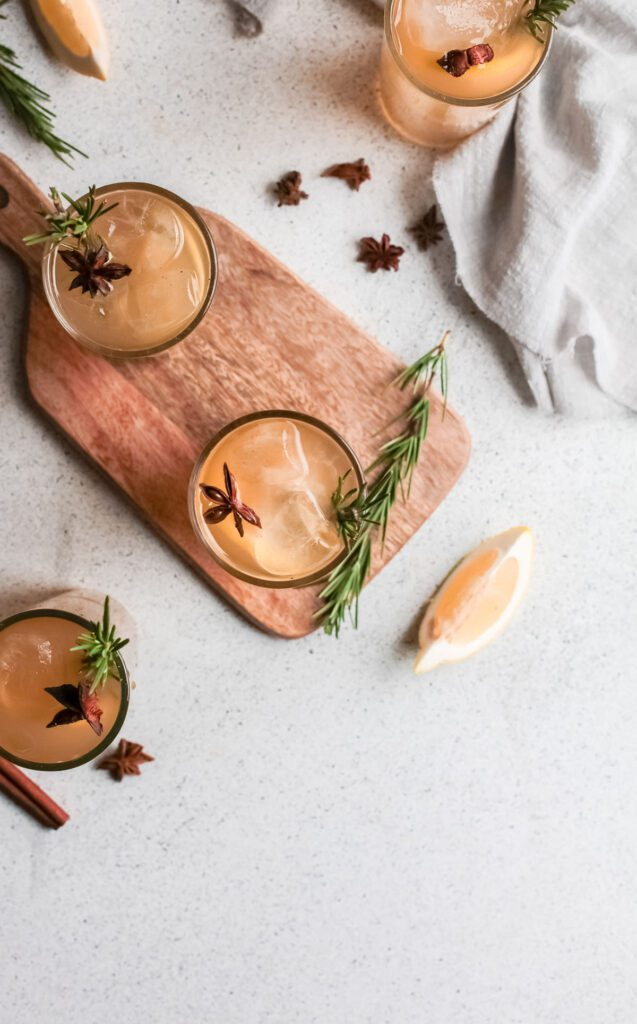 Three whiskey smashes from above on wood with rosemary, lemon and star anise