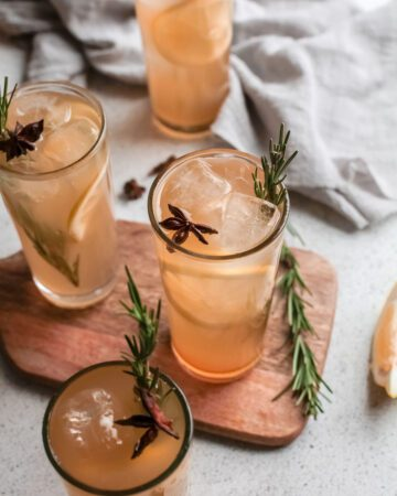Four Pumpkin Whiskey Smash drinks garnished with rosemary