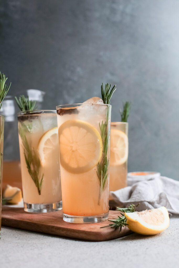 Three pumpkin cocktails on wood garnished with lemon and rosemary