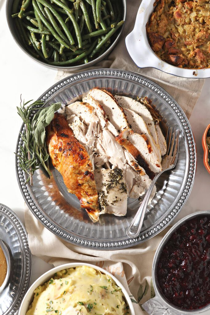 Sliced turkey breast on a silver platter with other sides