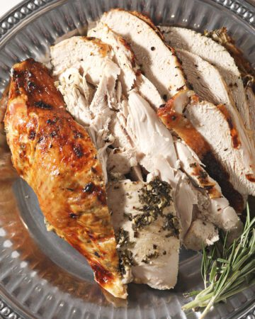 Sliced herb butter turkey breast on a silver tray