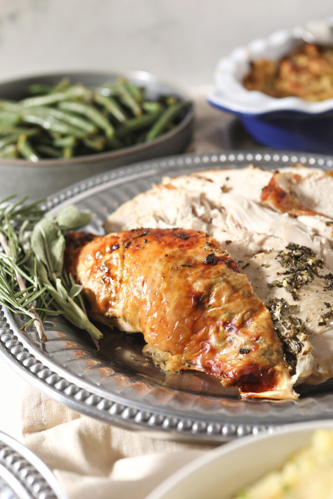 Sliced herb butter turkey breast on a tray with herbs