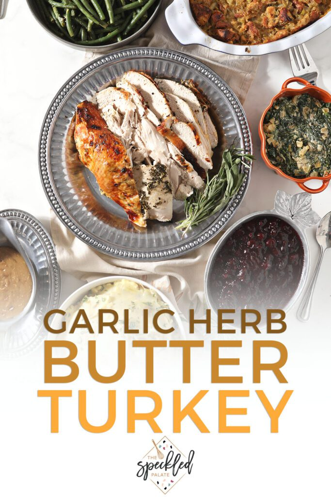 Sliced turkey on a tray with other sides with the text garlic herb butter turkey