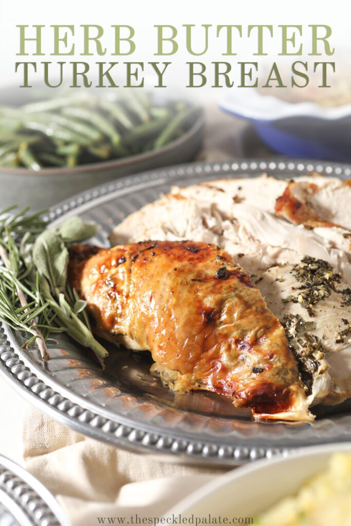 Sliced turkey breast on a silver platter with the text herb butter turkey breast
