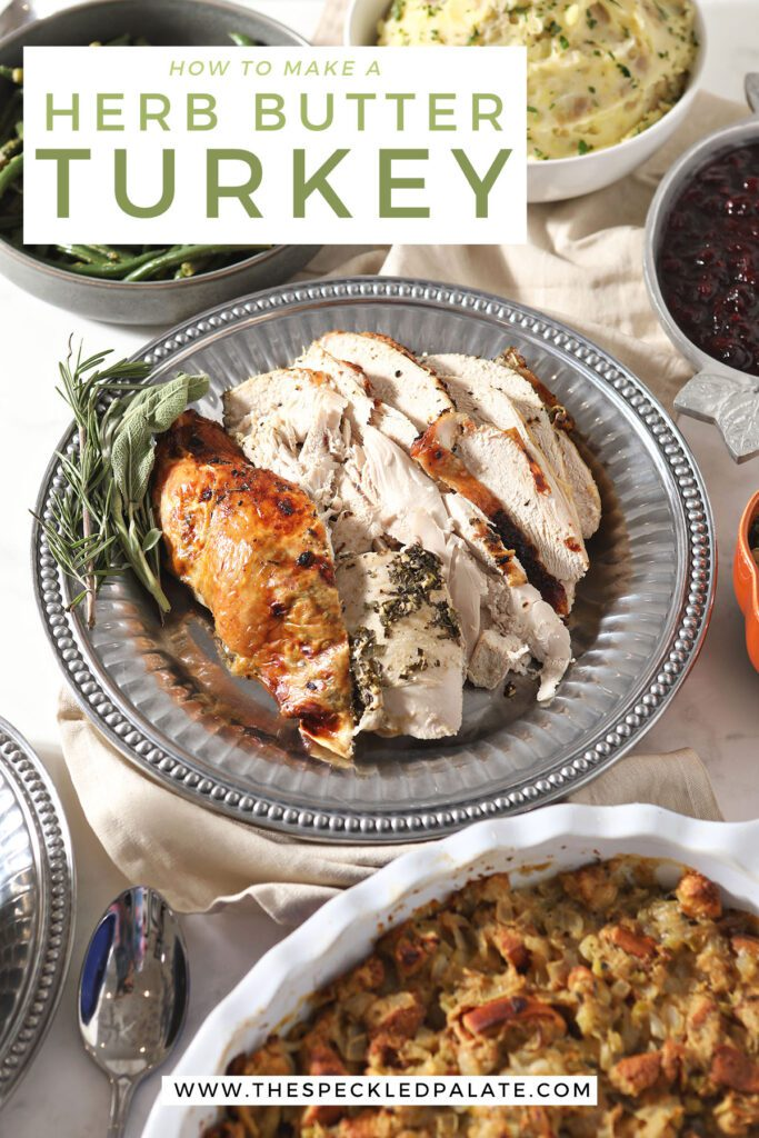 Sliced turkey on a silver platter with sides with the text how to make herb butter turkey