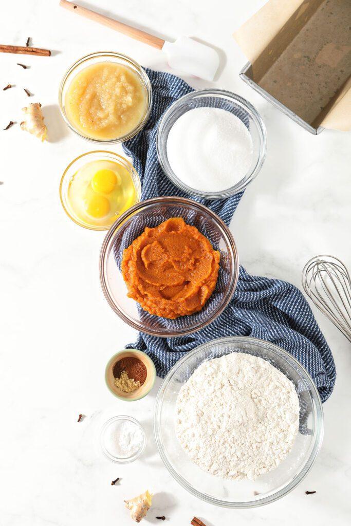 Pumpkin bread ingredients in bowls on marble
