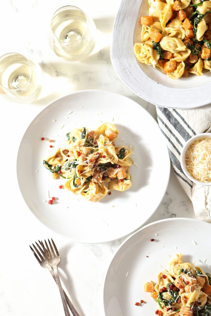 Two servings of butternut squash pasta on white plates