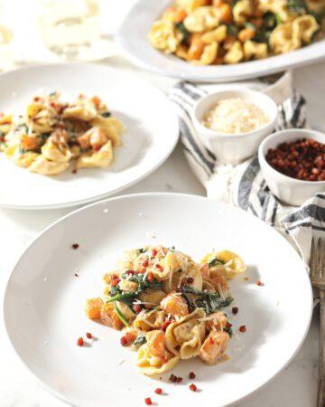 Three plates holding servings of creamy Tortellini Butternut Squash Pasta